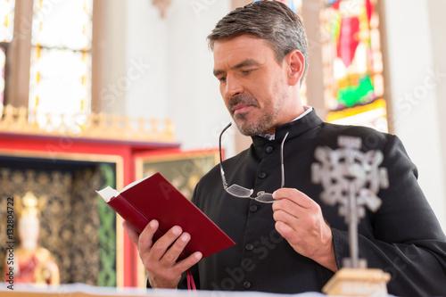 Obraz na plátne Priester liest Bibel in Kirche vor dem Altar