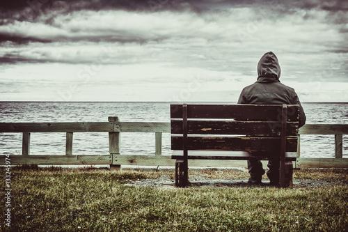 Man sitting on bench overlooking sea Fototapeta