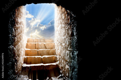 Easter resurrection background, with empty stone tomb and light rays from the clouds
