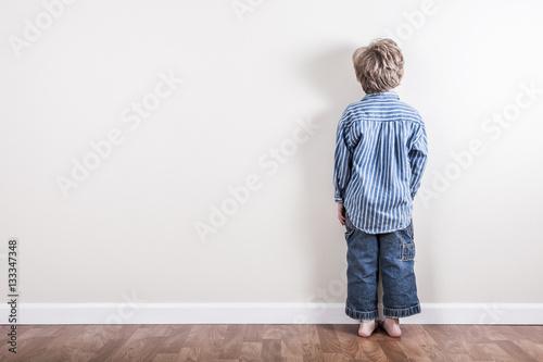 Fotografia Boy standing up against a wall