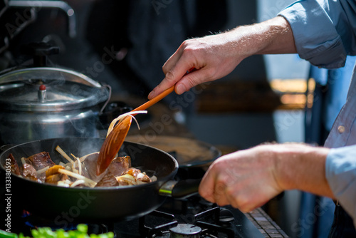 Vászonkép Man mixing the meat in a frying pan shovel