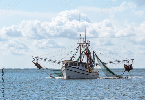 Marine shrimp fishing boat in Gulf of Mexico with nets out to catch seafood