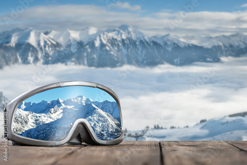 Ski goggles with reflection of mountains.