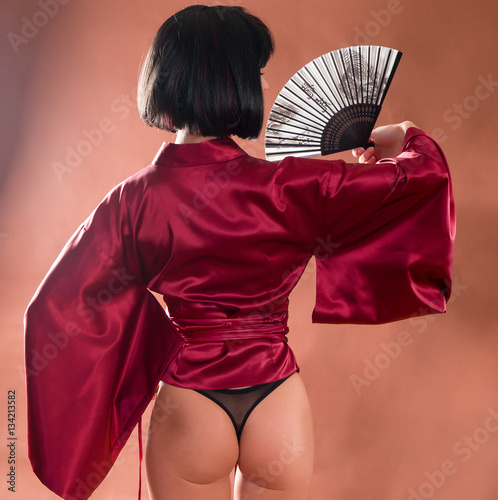 Valokuvatapetti sexy geisha in Japanese red kimono with a fan. Back view female