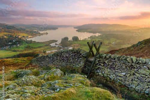 Fototapeta Beautiful sunset over Windermere in the Lake District with a stile and stone wall in the foreground