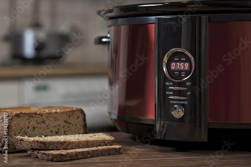Slow Cooker (Schongarer) in der Küche zusammen mit einem angeschnitteten Brot