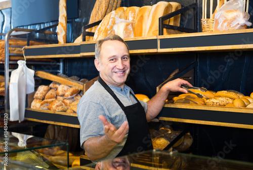Foto Portrait of  baker with fresh bread smiling in bakery