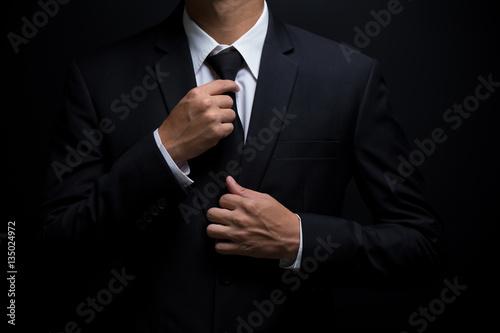 Valokuva Man in black suit and adjusting his necktie