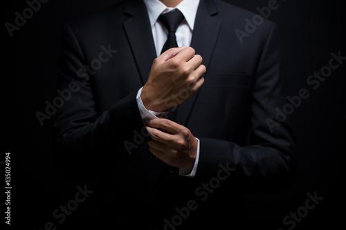 Valokuvatapetti Businessman adjusting his cufflinks