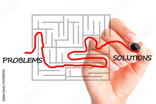 Finding solutions for problems concept suggested by a woman's hand solving a maze