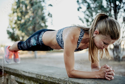 Fit girl doing plank exercise outdoor in the park warm summer day. Concept of endurance and motivation.