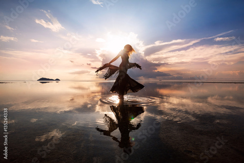 Fotografering Elegant woman dancing on water. Sunset and silhouette.