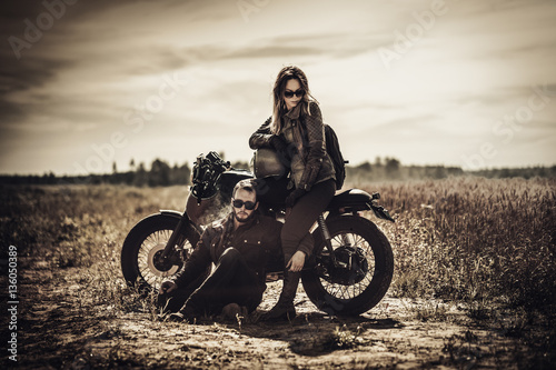 Fotografia Young, stylish cafe racer couple on vintage custom motorcycles in field