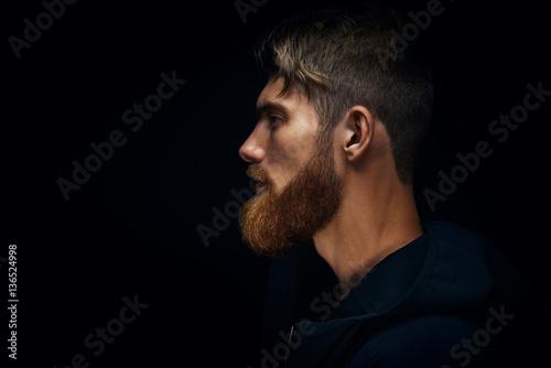 Fotografia Close-up image of serious brutal bearded man on dark background