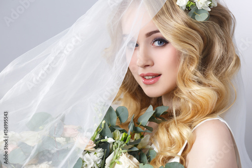 Photo Beauty portrait of a beautiful blonde bride in veil with a bouquet of flowers in his hands on a gray background
