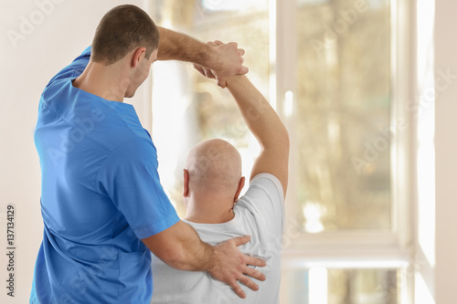 Tableau sur Toile Physiotherapist working with elderly patient in clinic