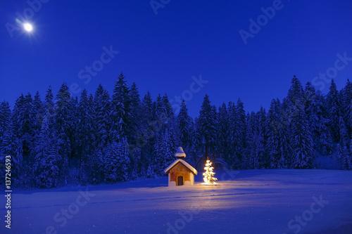 Obraz na płótnie Illuminated Christmas tree in front of a chapel in winter, Bavaria, Upper Bavari