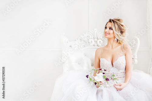Tela Young bride is sitting in white armchair