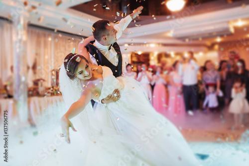 Fototapeta Happy bride and groom their first dance