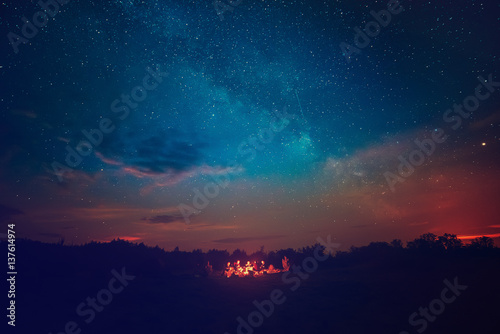 Leinwand Poster Camping fire under the amazing blue starry sky with a lot of shining stars and clouds