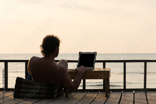 Fotografie, Obraz Digital nomad working online on the beach and seeing beautiful sunset