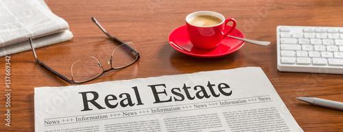 A newspaper on a wooden desk - Real Estate