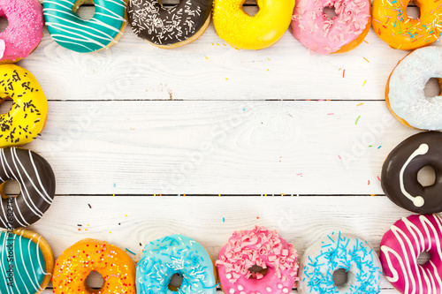 Colorful donuts on light wooden background Fototapet