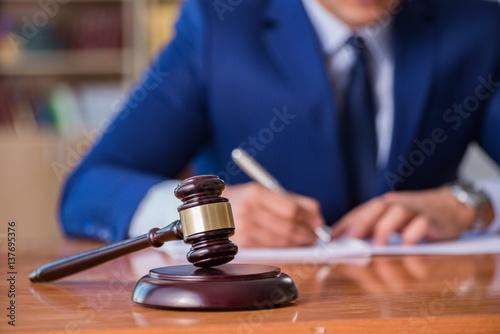 Obraz na płótnie Handsome judge with gavel sitting in courtroom