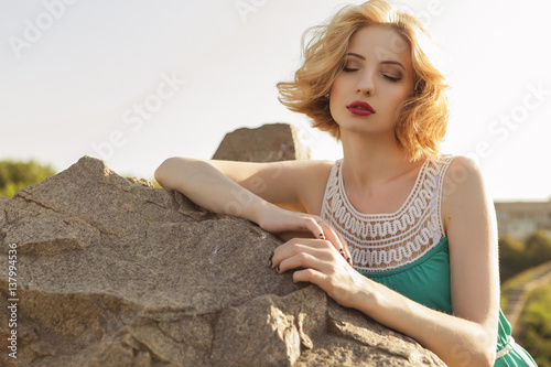 Stampa su Tela Beautiful blonde woman with curly short bob hairstyle, delicate make up and red lips in green short dress at the park