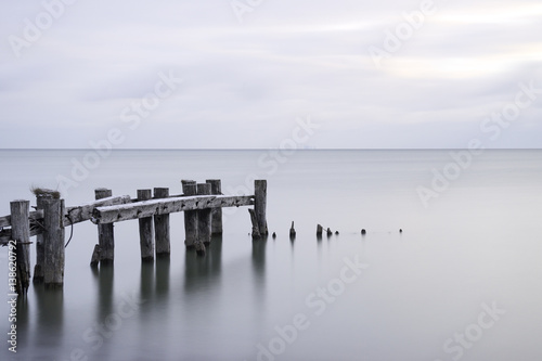 Posts of a broken pier leading out into calm blue tranquil sea water