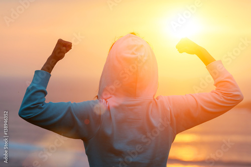 Back view of strong motivated woman celebrating workout goals towards the sun. Morning healthy training success.