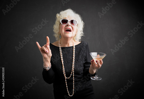 Fototapeta Cool grandmother with sunglasses and drink in hand
