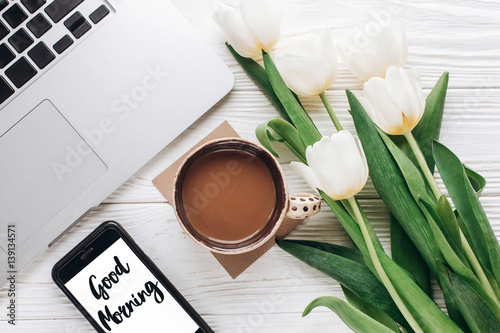 Fotografia good morning text sign on phone screen and laptop with morning coffee and tulips on white wooden rustic background