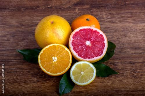 Leinwand Poster citrus fruit ( lemon, orange, grapefruit and tangerine) with leaves