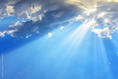 Leinwand Poster Sun light rays or beams bursting from the clouds on a blue sky