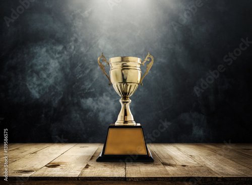 Obraz na plátně champion golden trophy placed on wooden table with dark background copy space ready for your design