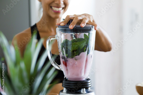 Canvas Print Woman blending spinach, berries, bananas and almond milk to make a healthy green