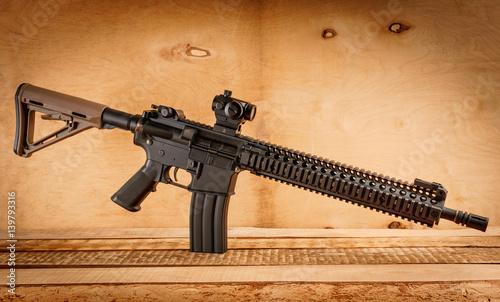 Fotografie, Obraz black assault rifle on an old wooden table