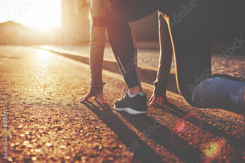 Athlete woman in running start pose on the city street. Sport tight clothes. Bright sunset, blurry background. Horizontal