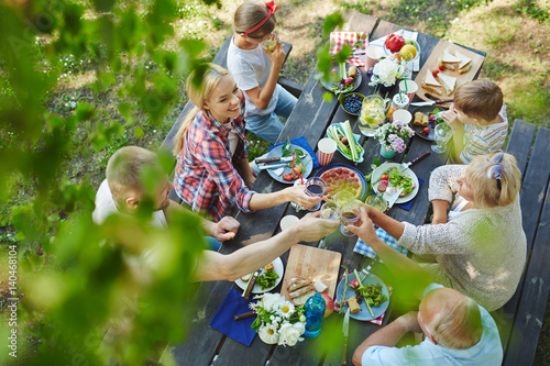 Stampa su Tela Adults toasting with wineglasses by served table during family dinner
