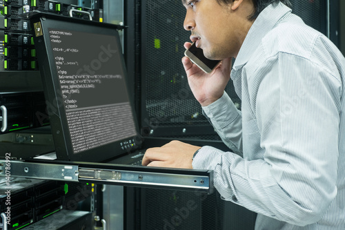 Photographie system administrator talk telephone to consult in data center