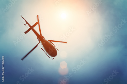Fototapeta Helicopter flying in the blue sky with sun