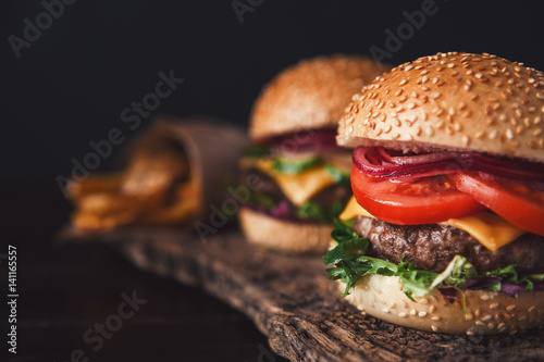 Fotografia two mouth-watering, delicious homemade burger used to chop beef