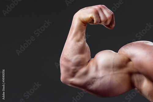 Canvas bodybuilding naked male arm with biceps on grey background