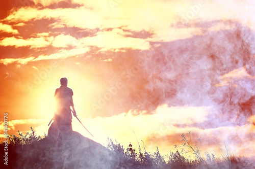 Fototapeta Silhouette of a warrior with a sword in the smoke of a mountain war