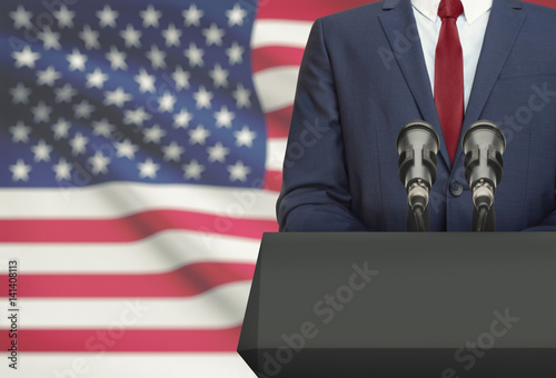 Fotografia Businessman or politician making speech from behind a pulpit with national flag