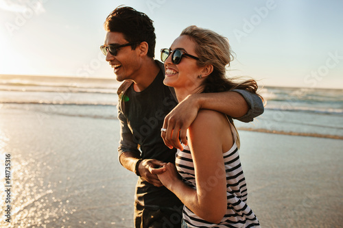 Smiling young couple walking on beach
