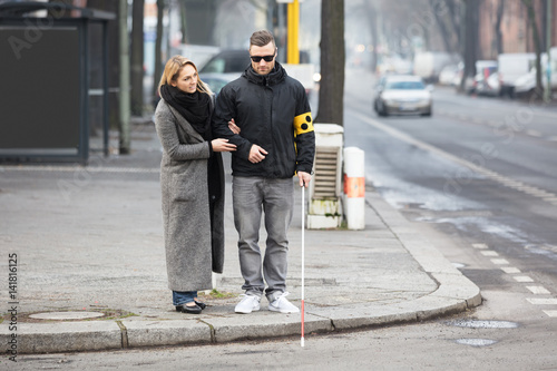 Tablou Canvas Woman Assisting Blind Man On Street