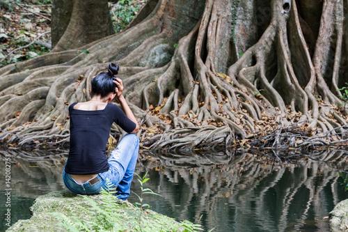 Desperate woman seating alone in nature in front of beautiful banyan and river, Fototapeta