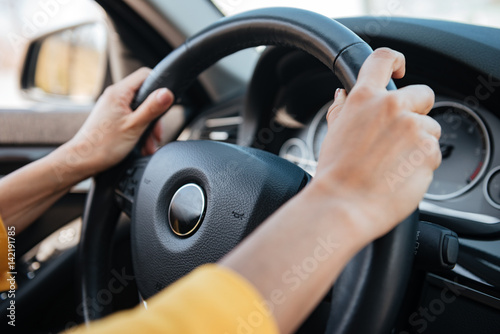 Tablou Canvas Female hands on steering wheel while driving a car